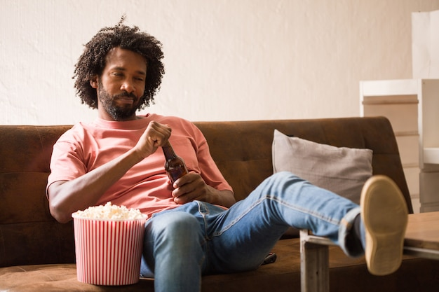 Young african man watching a movie holding a popcorn bucket and drinking a beer. Premium Photo