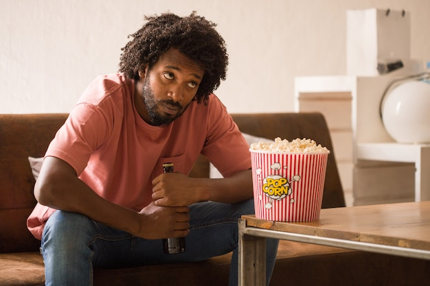 Young african man watching television, he is bored, holding a popcorn bucket. Premium Photo