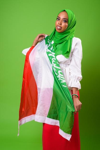 緑の壁とクロマキーに対して若いアフリカのイスラム教徒の女性 Premium写真