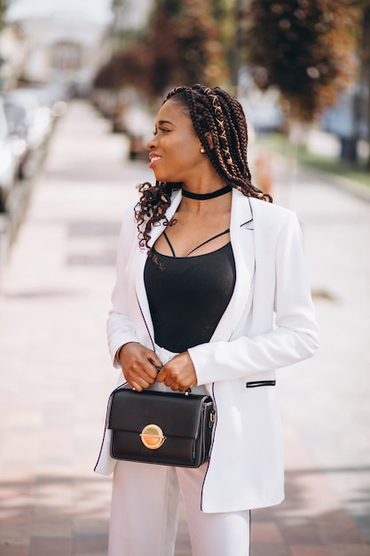 Young african woman dressed in white suit outside the street Free Photo