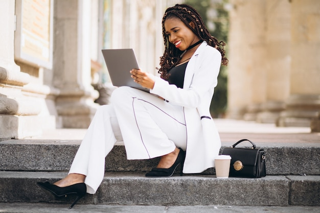 Young african woman dressed in white using laptop Free Photo