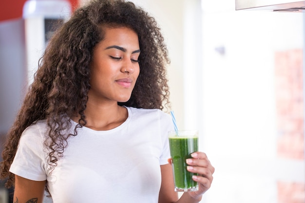 젊은 아프리카 여성은 체중 감소와 해독을위한 건강한 채식 스무디를 즐길 수 프리미엄 사진