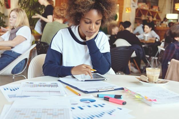 Молодая африканская женщина-предприниматель с серьезным сосредоточенным выражением лица сидит в коворкинг-кафе с компьютером и бумагами с сенсорной панелью, анализирует финансовую информацию на планшете, положив локоть на стол Бесплатные Фотографии