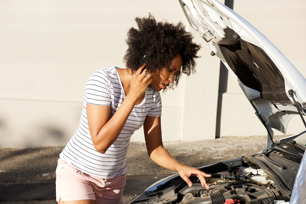 Young african woman standing by broken down car parked on the road and calling for assistance Premium Photo