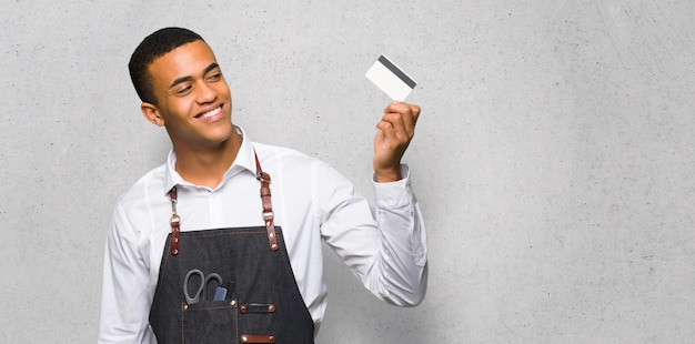 Young afro american barber man holding a credit card and thinking on textured wall Premium Photo