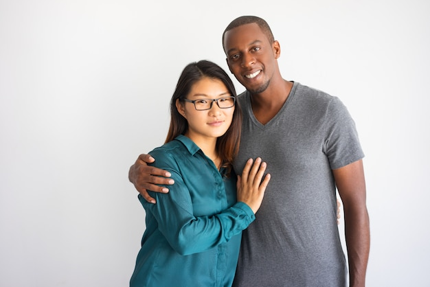 Young afro american man hugging his asian girlfriend with glasses. Free Photo