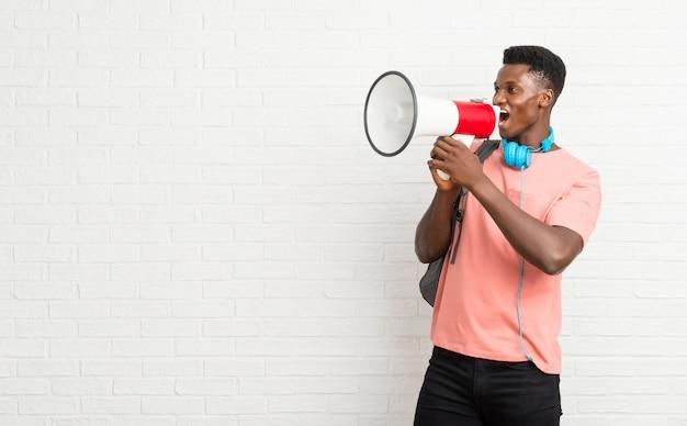 メガホンを持つ若いアフロアメリカ人の男子学生 Premium写真