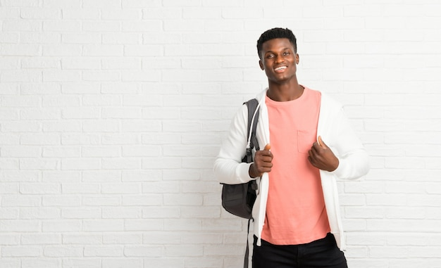 Young afro american man student proud and self-satisfied in love yourself concept Premium Photo