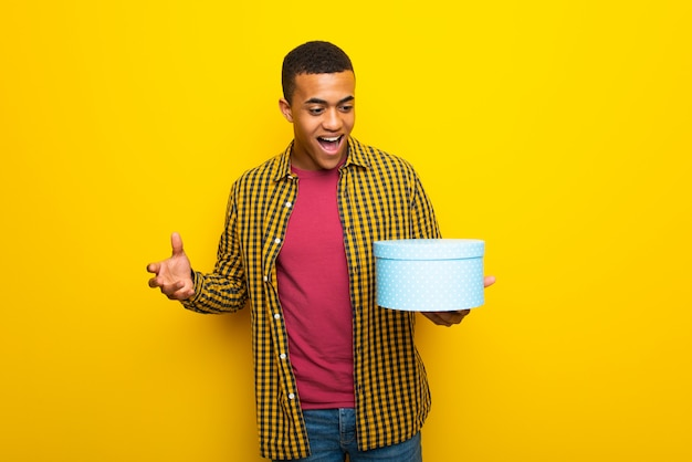 Young afro american man on yellow background holding gift box in hands Premium Photo