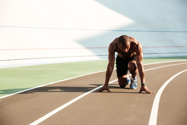Giovane uomo afroamericano di sport nella posizione di partenza pronto per iniziare sulla pista di sport allo stadio Foto Gratuite