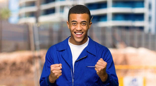 Young afro american worker man celebrating a victory in winner position in a construction site Premium Photo