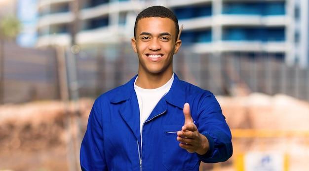 建設現場でかなりの取引を閉じるために握手する若いアフロアメリカンワーカー男 Premium写真