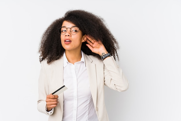 Young afro business woman holding a credit car isolated young afro business woman holding a credit cartrying to listening a gossip. Premium Photo