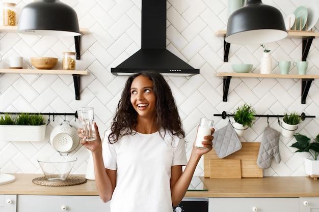 La giovane ragazza afro tiene due bicchieri con acqua e latte Foto Gratuite