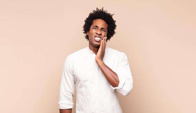 Молодой афро-мужчина держится за щеку и страдает от болезненной зубной боли, чувствует себя плохо, несчастно и несчастно, ищет стоматолога Premium Фотографии