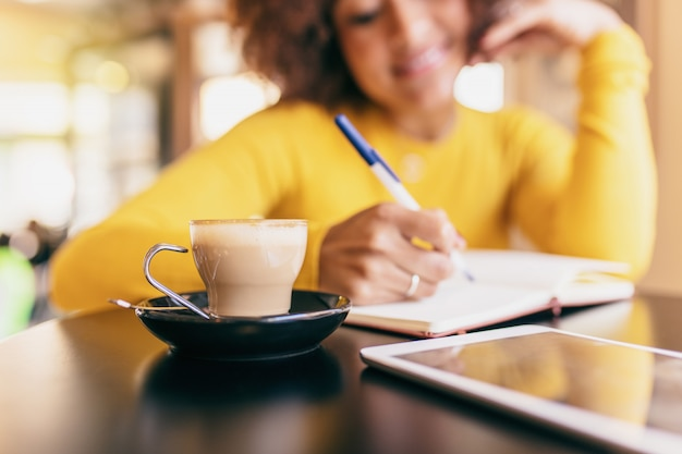Young afro woman at cafe. she is writing in a notebook, closeup of a coffee. Premium Photo