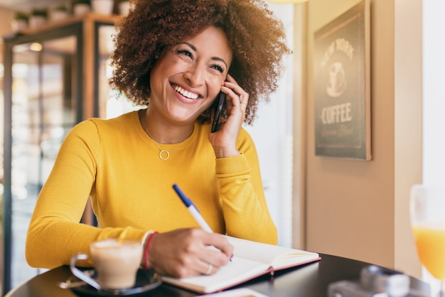 Young afro woman in a coffee shop, smiling and confident, talking on a mobile phone. Premium Photo