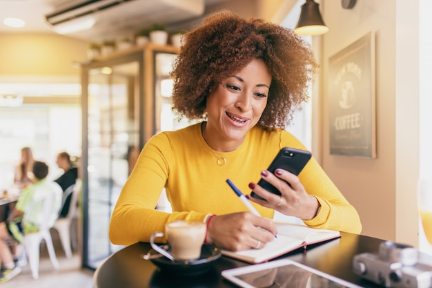 Young afro woman in a coffee shop, using her mobile phone and writing in a notebook Premium Photo