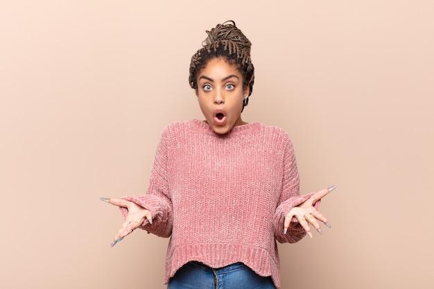 非常にショックを受けて驚いた若いアフロ女性 Premium写真