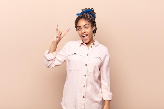 幸せ、楽しさ、自信、前向きで反抗的な感じ、手で岩や重金属の看板を作る若いアフロ女性 Premium写真