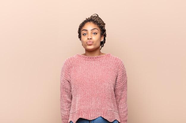 Молодая афро-женщина нервничает и полна надежд, скрещивает пальцы, молится и надеется на удачу Premium Фотографии