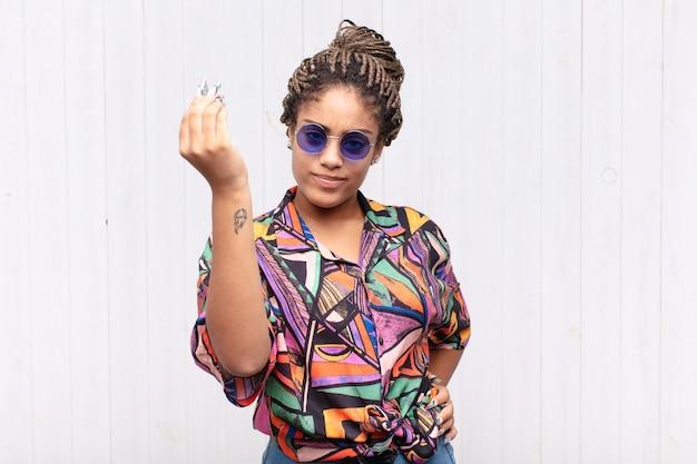 資本またはお金のジェスチャーを作る若いアフロ女性 Premium写真