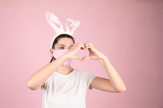 Женщина молодого возраста в маске защиты от коронавируса для эпидемии covid-19 делает форму символа сердца руками на розовом Premium Фотографии
