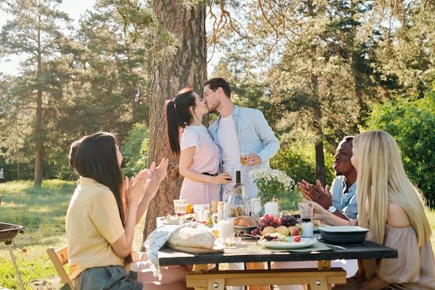 彼らの友人が手をたたくことによって婚約で彼らを祝福している間、提供されたテーブルによって松の木の下でキスしている若い好色なカップル Premium写真
