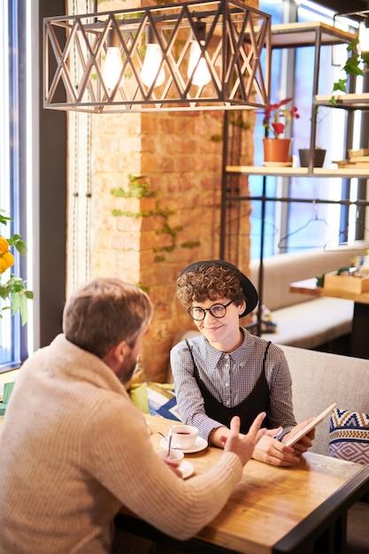 豪華なカフェやレストランに座ってオンラインビデオを議論するタッチパッドと好色なカップル Premium写真