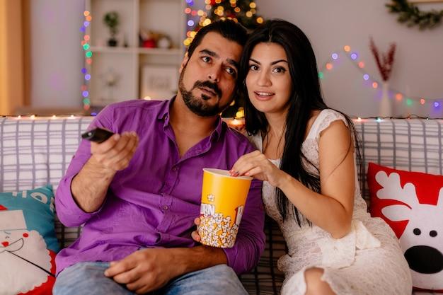 Молодая и красивая пара счастливая женщина и мужчина сидят на диване с ведром попкорна и смотрят телевизор вместе в украшенной комнате с рождественской елкой на заднем плане Бесплатные Фотографии
