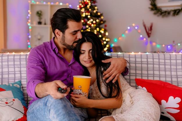 Молодая и красивая пара, сидящая на диване, мужчина и женщина с ведром попкорна, вместе смотрят телевизор, счастливы в любви в украшенной комнате с рождественской елкой на заднем плане Бесплатные Фотографии