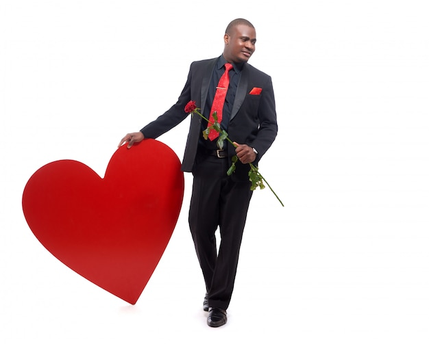 Молодой и уверенный африканский мужчина в люксе и красном галстуке держит красную розу Бесплатные Фотографии