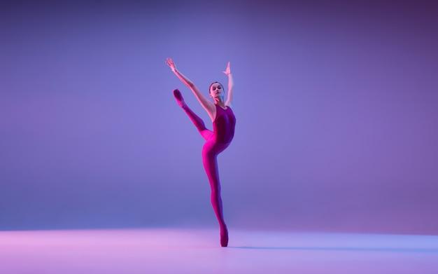 ネオンの光の中で紫色のスタジオの背景に分離された若くて優雅なバレエダンサー 無料写真