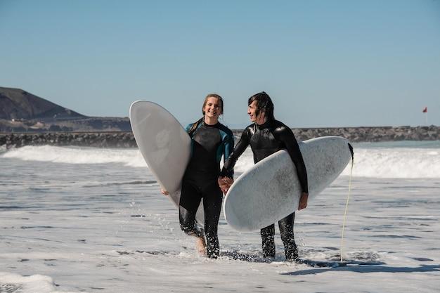 Молодая и счастливая улыбающаяся пара серферов в черных гидрокостюмах, держащих друг друга за руки и идущих в воде с досками для серфинга Premium Фотографии