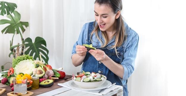 デニムの服で、明るい背景にテーブルで有機野菜のサラダを食べる若いと幸せな女。健康的な自家製食品のコンセプト。 無料写真