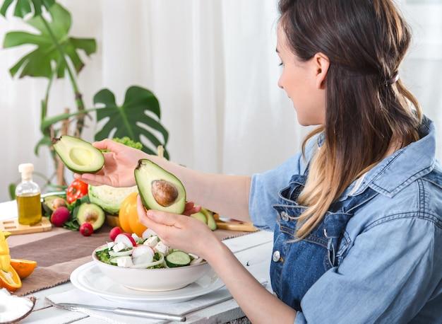 Молодая и счастливая женщина смотрит на авокадо за обеденным столом Бесплатные Фотографии