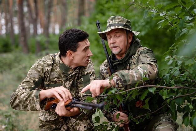 Молодые и старшие охотники за мужчинами заряжают ружья. Premium Фотографии