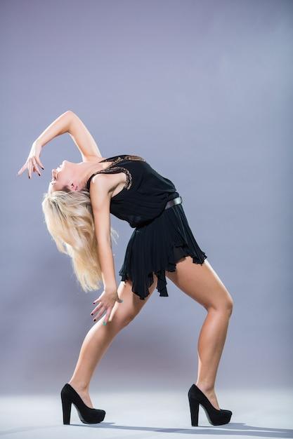 회색 배경에 포즈 젊고 세련된 댄서 무료 사진
