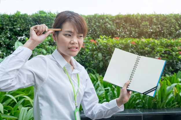 Young angry confused working woman face hold notebook and pencil point her head. Premium Photo