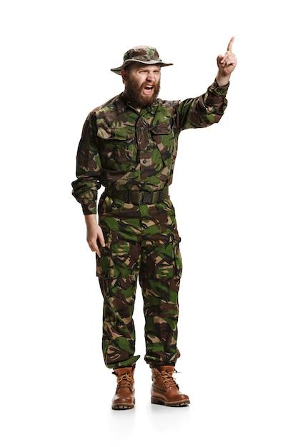白いスタジオに分離された迷彩服を着ている若い怒っている猛烈な兵士 無料写真