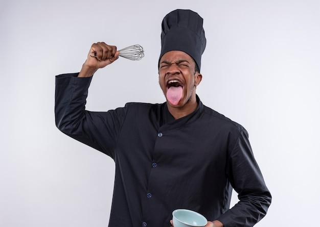 シェフの制服を着た若いイライラするアフリカ系アメリカ人の料理人は、コピースペースで白い背景に分離されたボウルと泡立て器の舌を保持 無料写真