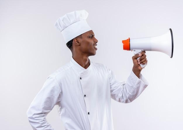 シェフの制服を着た若いイライラするアフリカ系アメリカ人の料理人は、コピースペースと白い背景で隔離のラウドスピーカーを保持します。 無料写真