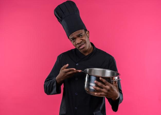 シェフの制服を着た若いイライラするアフリカ系アメリカ人の料理人は、コピースペースでピンクの背景に分離された手で鍋とポイントを保持します 無料写真