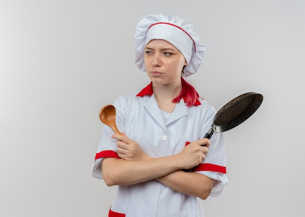 Il giovane chef femminile biondo infastidito in uniforme del cuoco unico attraversa le braccia e tiene la padella e il cucchiaio isolati sulla parete bianca Foto Gratuite