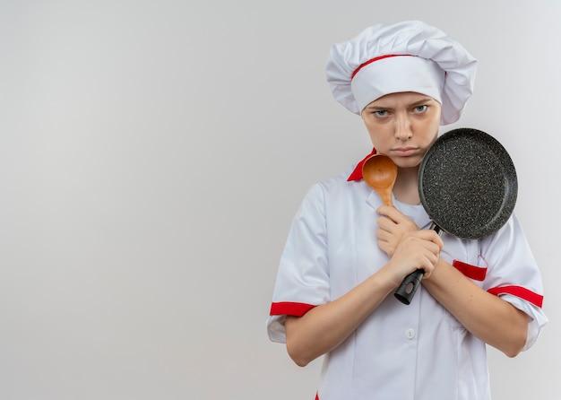 シェフの制服を着た若いイライラする金髪の女性シェフが腕を組んで、白い壁に隔離されたフライパンとスプーンを保持します。 無料写真