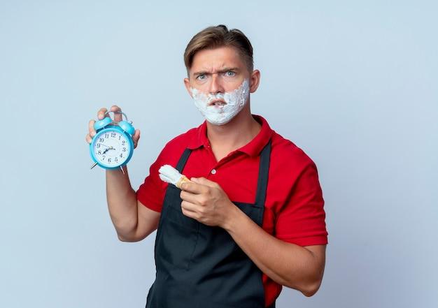 알람 시계를 들고 면도 브러시와 복사 공간이 흰색 공간에 고립 된 면도 거품으로 균일 한 얼룩진 얼굴에 젊은 화가 금발 남성 이발사 무료 사진