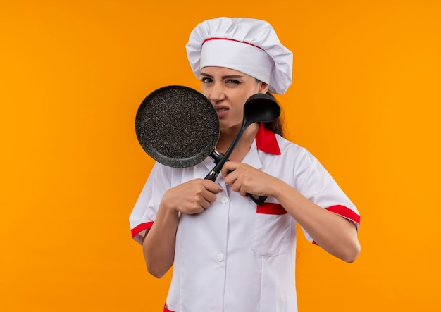 Young annoyed caucasian cook girl in chef uniform crosses frying pan and ladle isolated on orange background with copy space Free Photo