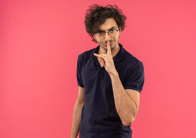 ピンクの壁に分離された光学メガネジェスチャー沈黙と黒いシャツの若いイライラ男 無料写真