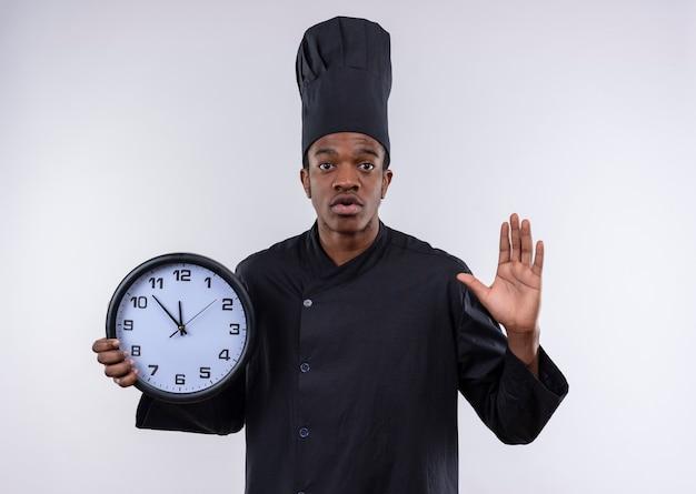 Giovane cuoco afro-americano ansioso in uniforme del cuoco unico tiene il segno della mano di arresto di gesti e dell'orologio isolato su fondo bianco con lo spazio della copia Foto Gratuite