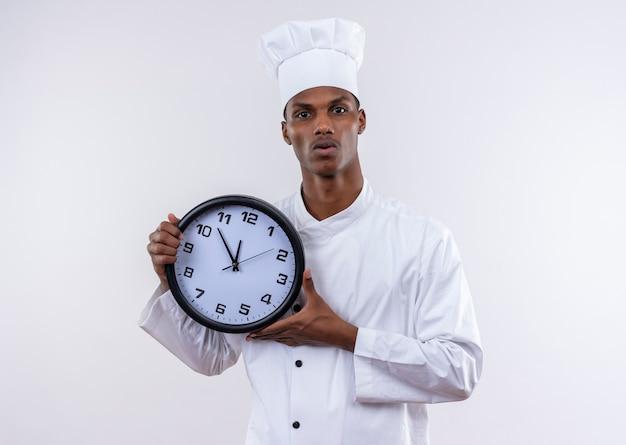 Il giovane cuoco afroamericano ansioso in uniforme del cuoco unico tiene l'orologio con entrambe le mani isolate su fondo bianco con lo spazio della copia Foto Gratuite